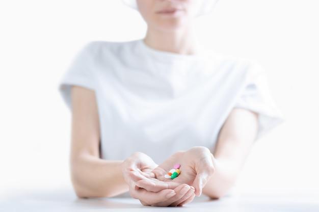 Mulher com roupa de hospital tem um conjunto de comprimidos nas palmas das mãos. o conceito de psique instável, tomando antidepressivos. mídia mista