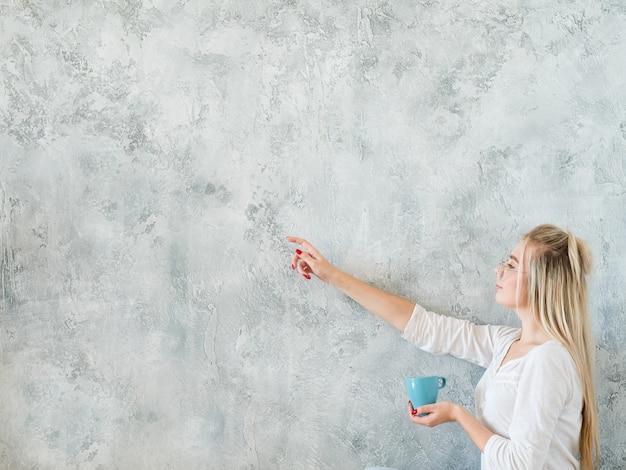 Mulher com roupa de lazer, apontando para a esquerda. xícara de chá na mão