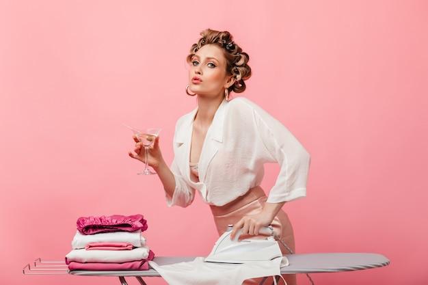 Mulher com roupa de seda clara posando na parede rosa com copo de martini e passando roupas