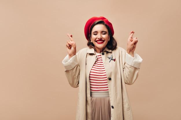 Mulher com roupa elegante de outono cruza os dedos sobre fundo bege. menina sorridente na boina vermelha e posando de casaco elegante.
