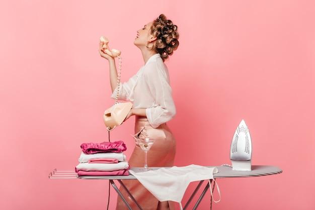 Mulher com roupa elegante sorrindo e falando no telefone fixo, posando na parede rosa com ferro