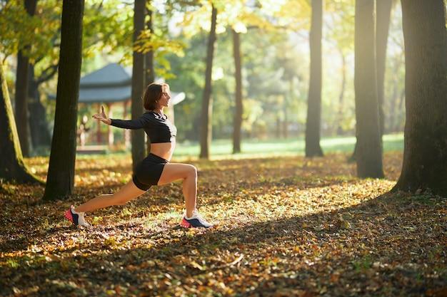 Mulher com roupa esportiva se aquecendo no parque antes de correr