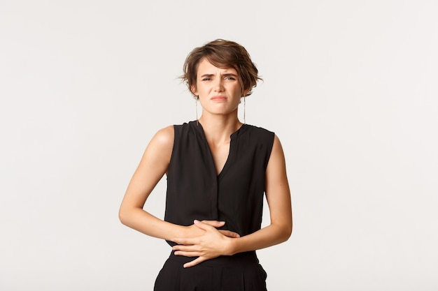 Mulher com roupa formal, tocando a barriga e fazendo careta de dor. menina com cólicas dolorosas ou dor de estômago, sensação de desconforto em pé.