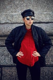 Mulher com roupa preta, jaqueta, boné e camisa vermelha, fica em pé nas pedras perto de um rio