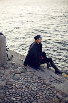 Mulher com roupa preta, jaqueta, boné e camisa vermelha sentada nas pedras perto de um rio no outono