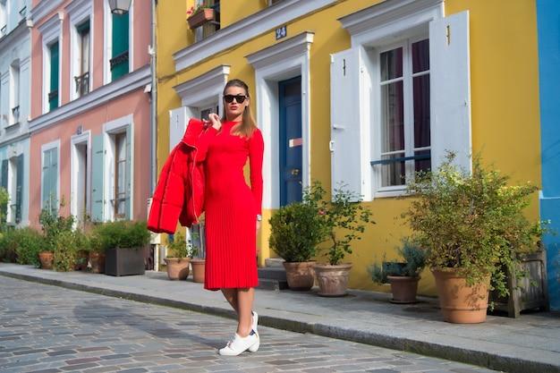 Mulher com roupa vermelha total desfrutar de uma bela caminhada pela rua paris. passeios despreocupados parisienses em dia ensolarado. vamos andar. atrativos de lazer e culturais em paris. guia para o tempo livre na capital francesa.