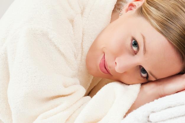 Mulher com roupão de banho em spa