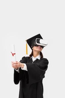 Mulher com roupão de formatura e boné usando fone de ouvido de realidade virtual