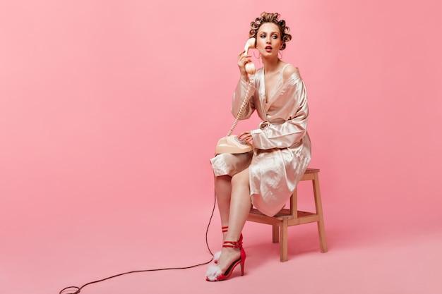 Mulher com roupão de seda com rolos de cabelo na cabeça está sentada na cadeira e falando no telefone na parede rosa