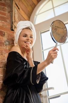 Mulher com roupão de seda, fazendo sua rotina diária de cuidados com a pele em casa.