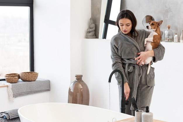 Mulher com roupão segurando cachorro enquanto no banheiro