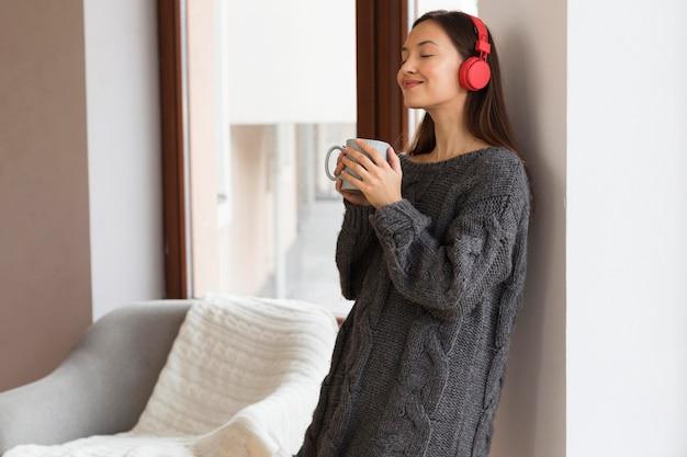Mulher com roupas aconchegantes com caneca e fones de ouvido