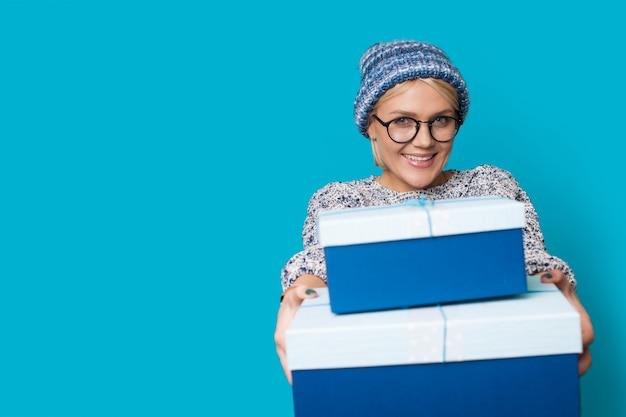 Mulher com roupas azuis e chapéu está sorrindo e dando caixas de presente para a câmera enquanto usa óculos na parede azul do estúdio