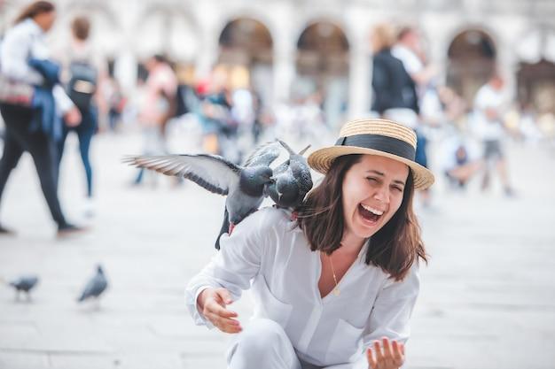Mulher com roupas brancas e chapéu de palha se divertindo com os pombos na praça da cidade de veneza na piazza san marco
