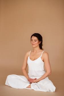 Mulher com roupas brancas em posição de lótus, sobre um fundo marrom. dia de yoga. meditação da manhã
