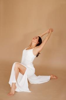 Mulher com roupas brancas faz yoga em um fundo marrom.