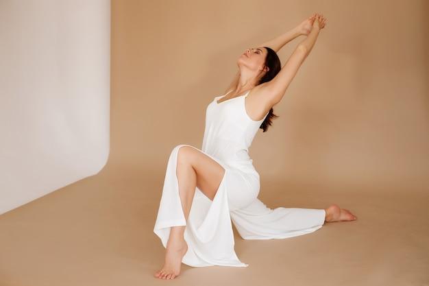 Mulher com roupas brancas faz yoga no fundo marrom. dia internacional da ioga.