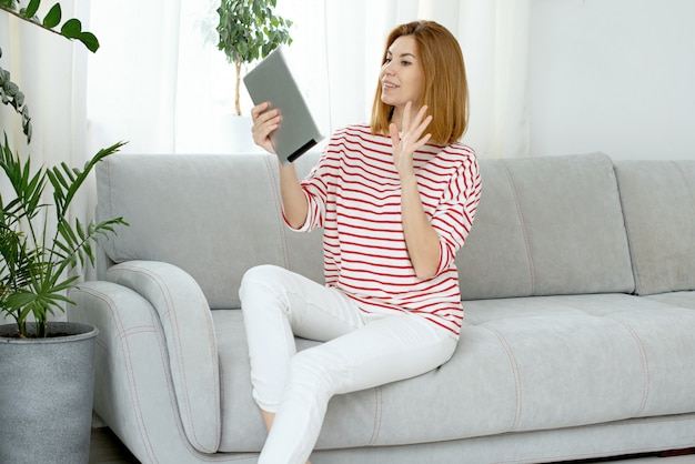 Mulher com roupas brancas se comunica por link de vídeo. conversando on-line e acenando para a tela do computador.