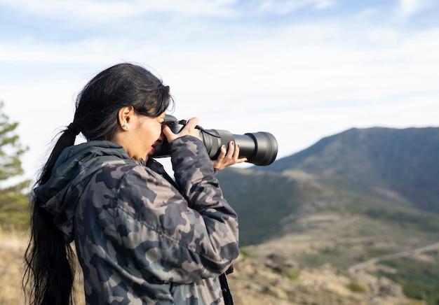 Mulher com roupas camufladas tirando fotos com lentes telefoto