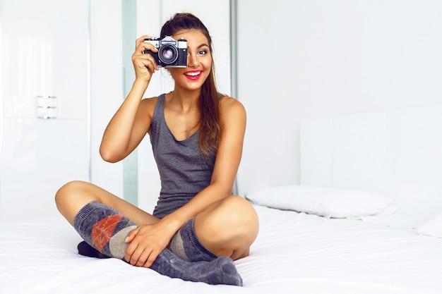 Mulher com roupas casuais aconchegantes, sentada em uma grande cama branca e tirando fotos com a câmera vintage