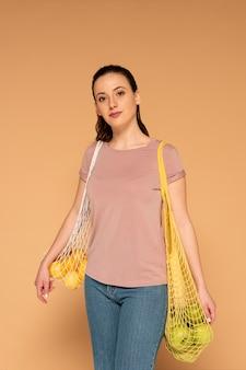 Mulher com roupas casuais carregando uma sacola reutilizável