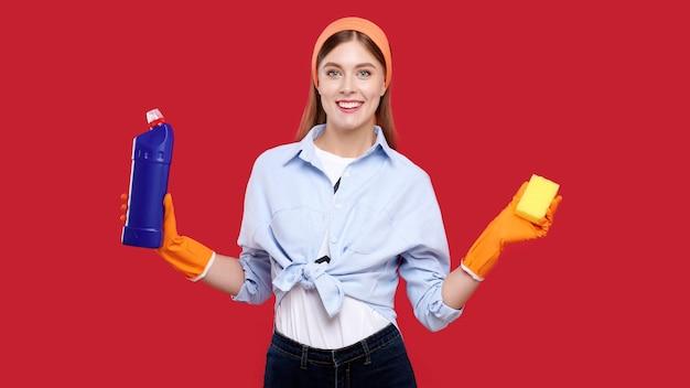Mulher com roupas casuais e luvas de borracha segurando produtos de limpeza