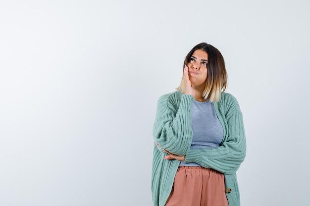 Mulher com roupas casuais, mantendo a mão na bochecha queimada e olhando pensativa, vista frontal.
