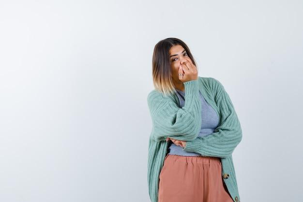 Mulher com roupas casuais, mantendo a mão no queixo e parecendo confiante, vista frontal.
