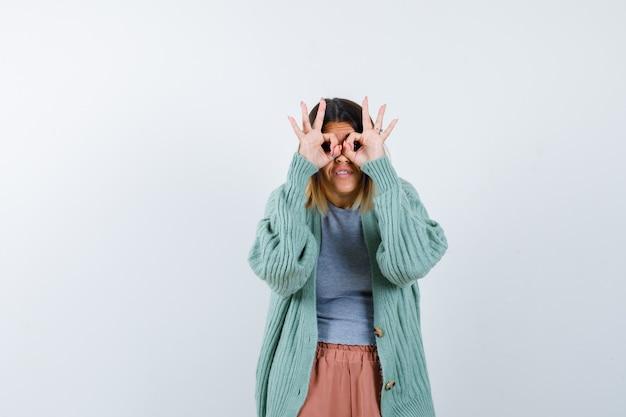 Mulher com roupas casuais, mostrando o gesto de óculos e olhando curiosa, vista frontal.