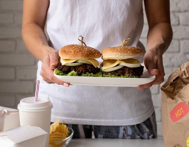 Mulher com roupas de casa desempacotando comida, entrega em domicílio com hambúrgueres, caixas de macarrão e bebidas