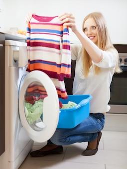 Mulher com roupas de cor perto da máquina de lavar