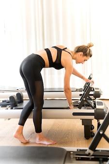 Mulher com roupas de ginástica, ajustando a cama de pilates do reformador