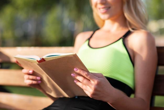 Mulher com roupas de ginástica lendo um livro