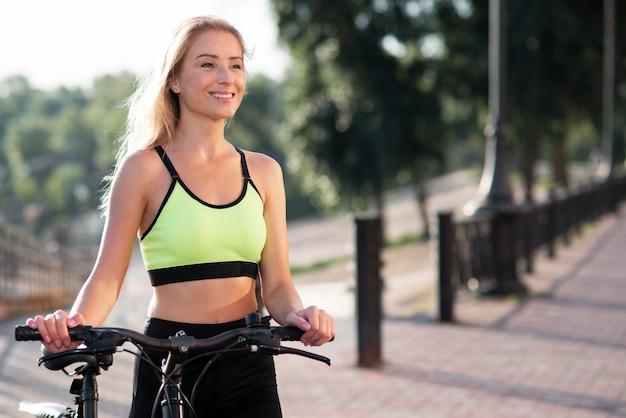 Mulher com roupas de ginástica segurando uma bicicleta
