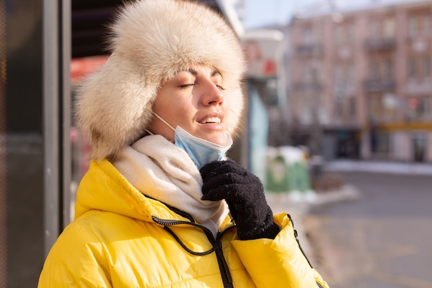 Mulher com roupas de inverno em um dia frio esperando um ônibus em um ponto de ônibus