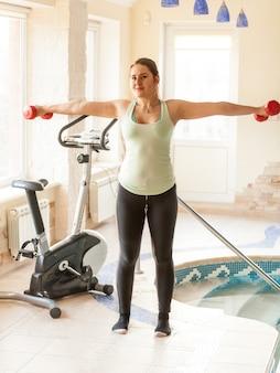 Mulher com roupas de treino, malhando com halteres na piscina