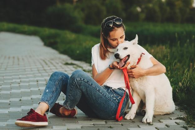 Mulher com roupas de verão sentada na calçada com as pernas cruzadas, abraçando e beijando um cachorro branco feliz com a boca aberta, olhando para a câmera