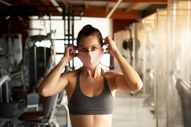 Mulher com roupas esportivas, colocando uma máscara e olhando para a câmera no ginásio.