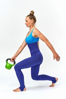 Mulher com roupas esportivas fazendo exercícios de balanço com pesos