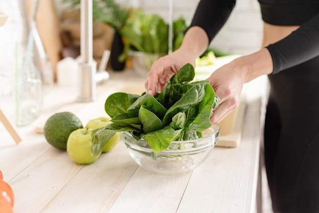 Mulher com roupas esportivas lavando espinafre na cozinha