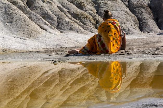 Mulher com roupas étnicas, sentada na margem do lago, de costas para o visualizador