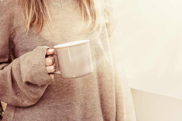 Mulher com roupas grandes, segurando um copo de bebida quente, atmosfera caseira.