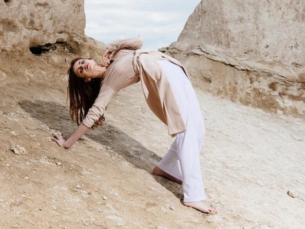 Mulher com roupas leves, posando sentada na areia perto das rochas.
