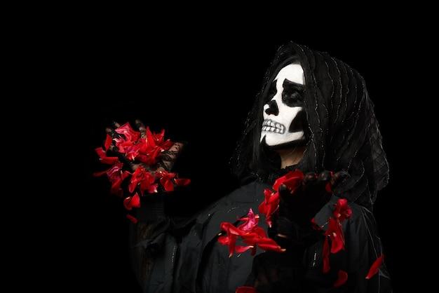 Mulher com roupas pretas e maquiagem de caveira