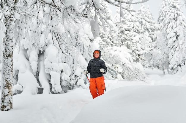 Mulher com roupas quentes, caminhando em uma floresta de inverno durante uma nevasca