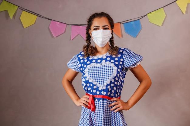 """Mulher com roupas típicas da famosa festa brasileira chamada """"festa junina"""" em comemoração a são joão."""