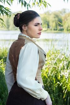 Mulher com roupas vintage na margem do rio