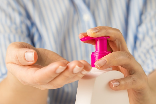 Mulher com sabonete líquido. lave o seu conceito de mãos