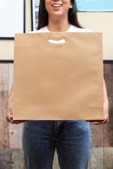 Mulher com saco de papel, pronto para entrega