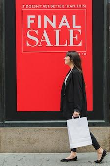 Mulher com sacola branca andando perto da loja